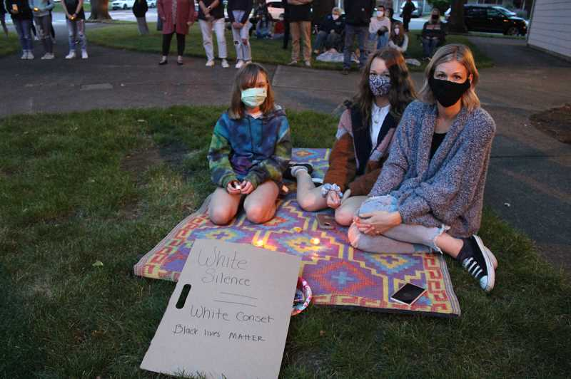 PMG PHOTO: KRISTEN WOHLERS - A Canby family sits in silence during the protest Thursday.