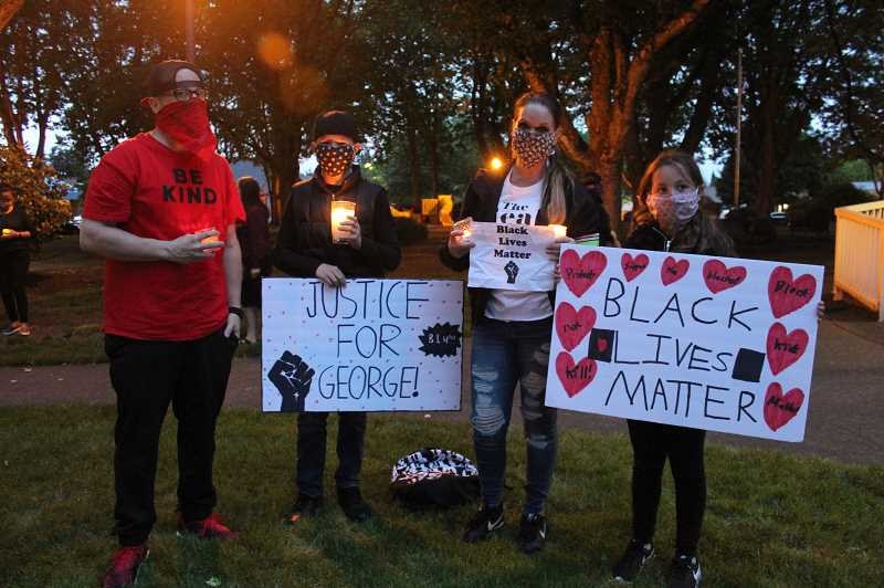 PMG PHOTO: KRISTEN WOHLERS - A family shows the signs they made for the vigil at Wait Park.