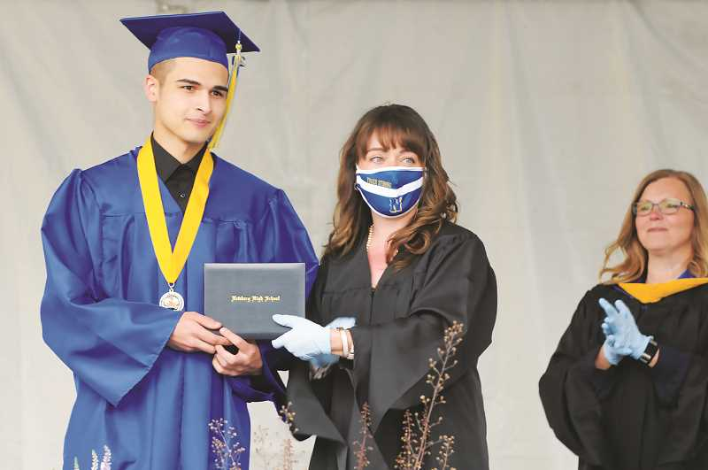 NEWBERG GRAPHIC: GARY ALLEN - NHS senior Aryc Hunt receives his diploma during the drive-thru ceremony Friday in the south parking lot of the school.