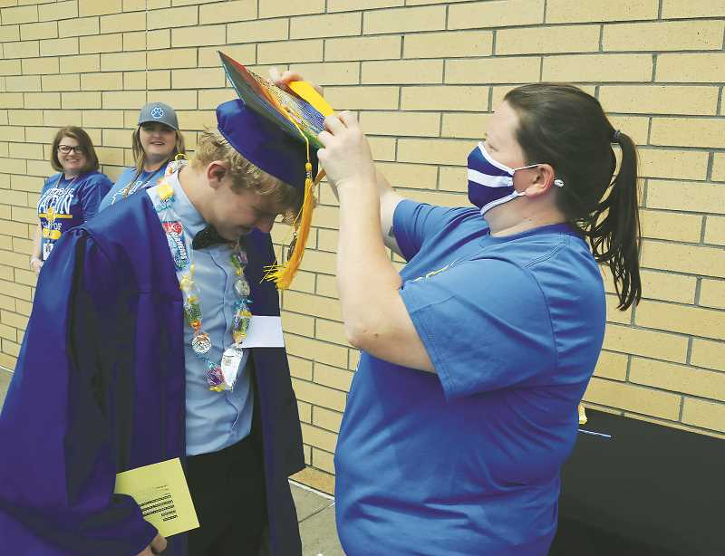 NEWBERG GRAPHIC: GARY  ALLEN - NHS behavior coach Sarah Malone metes a medal to senior Jordan Atkinson in a ceremony Friday afternoon at the school