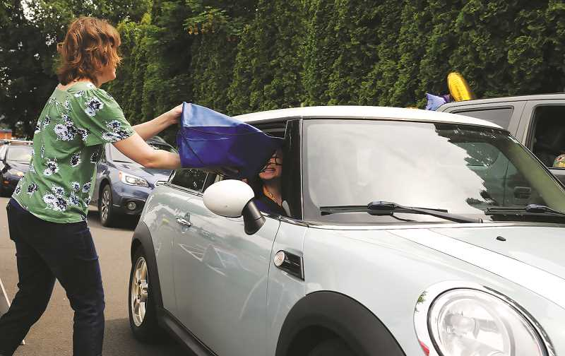 NEWBERG GRAPHIC: GARY ALLEN - Grads received a bag full of fun items, including a fethcing t-shirt as they departed the parking lot on Friday.