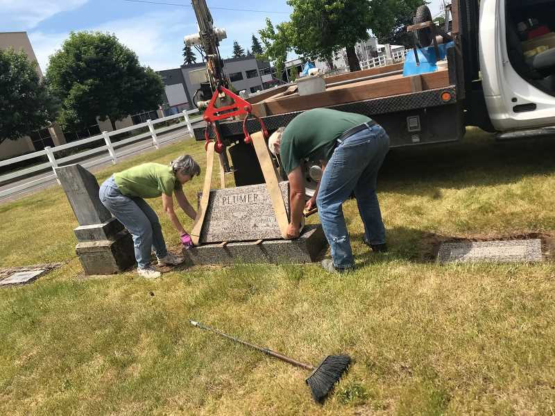 COURTESY PHOTO CAROL PALMER - Volunteers at Zion Memorial Cemetery begin work on straightening and repairing grave markers in the cemetery.