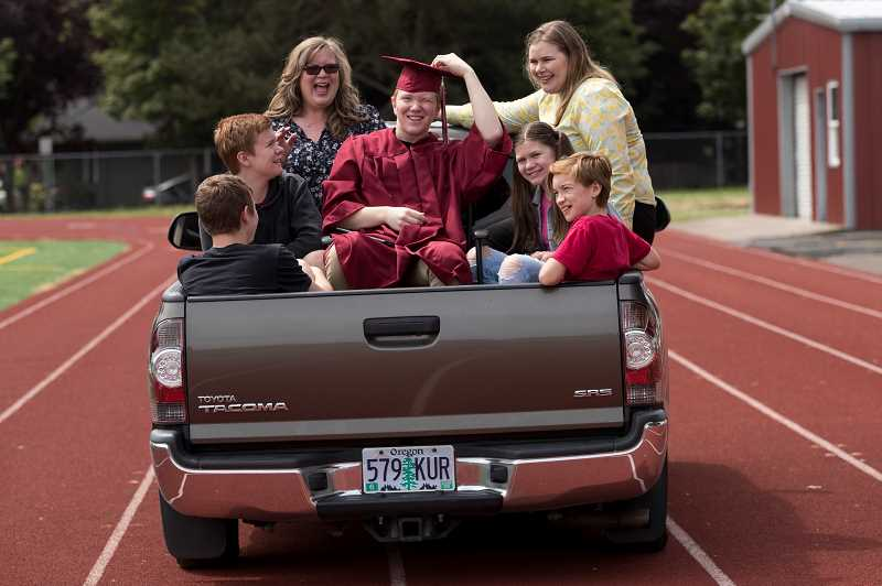 PMG PHOTO: JAIME VALDEZ - Dylan Robrecht sits in the back of his parents truck with his family after receiving his diploma on the first day of the drive-up graduations on the football field at Sherwood High School.