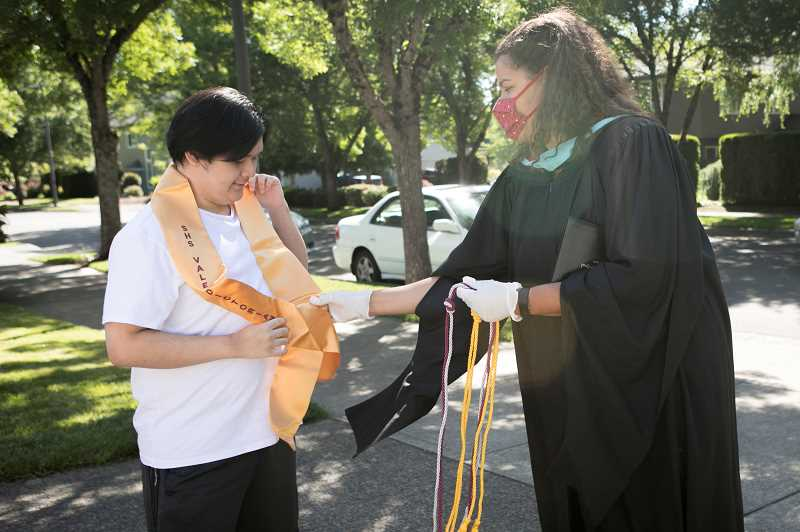 PMG PHOTO: JAIME VALDEZ - Sherwood High School Principal Melissa Baran delivers a sash and academic cords to Valedictorian Andrew Le at his home on June1.