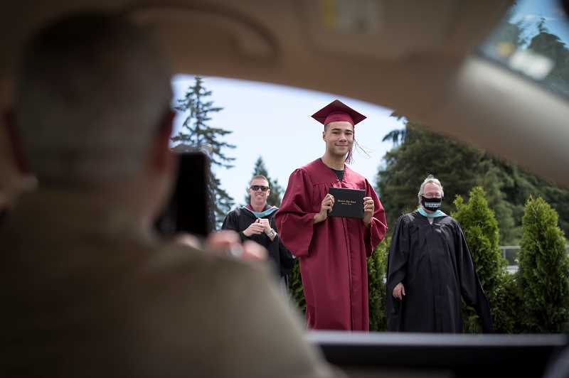 PMG PHOTO: JAIME VALDEZ - Sebastian Alexander poses for a picture for his mom, Christine Cuel, with diploma in hand during the first day of the drive-up graduations June 2, on the football field at Sherwood High School.