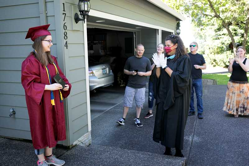 PMG PHOTO: JAIME VALDEZ - Angel Bowe smiles after she was given her diploma from Sherwood High School Principal Melissa Baran as her family watches on Monday, June 1. Bowe's twin sister, Maliyah, was planning to receive her diploma during a drive-up ceremony at the high school later in the week.