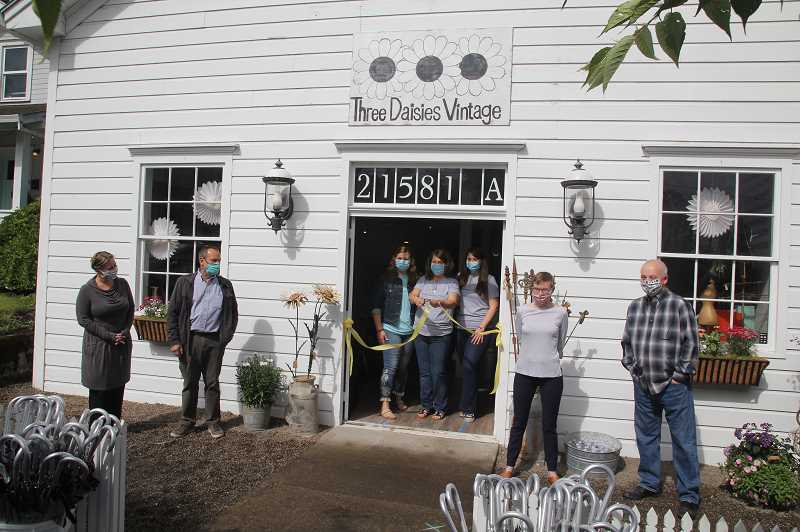 PMG PHOTO: JUSTIN MUCH - Three Daisies Vintage holds its ceremonial ribbon cutting on Saturday, June 6. Proprietors April Marcell, center, and her daughters Kayla, left, and Mackenzie, right, do the honors while accompanied by Aurora city councilors, left to right, Tara Weidman, Tom Heitmanek, Mercedes Rhoden-Feely and John Berard.