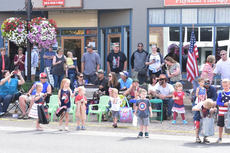 PMG FILE PHOTO - Attendees of last year's Estacada Fourth of July parade admire floats and search for candy.