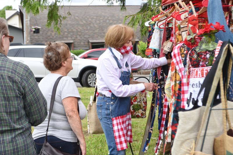 PMG PHOTO: BRITTANY ALLEN  - Peggy Price of Magnolia Designs shows off some of her handmade aprons to customers at the June 5 market.