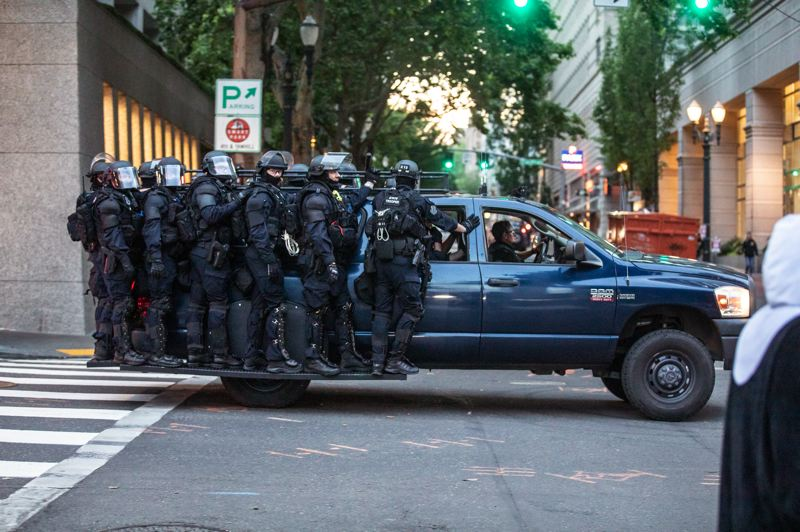 PMG PHOTO: JONATHAN HOUSE - Portland Police Bureau officers dressed in riot gear patrolled downtown during a recent protest.
