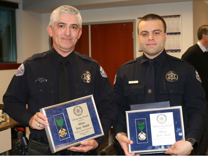 PMG FILE PHOTO - Woodburn police officers Jorge Gaspar, left, and Jacob Stout were given Lifesaving Medals last year. On Wednesday, one of the two was placed on administrative leave and the school resource officer program has been temporarily halted.