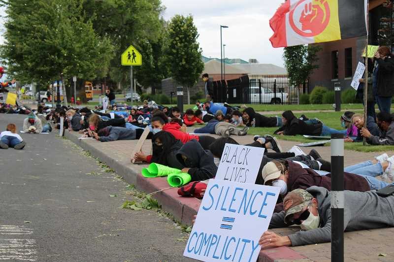 TERESA JACKSON/MADRAS PIONEER - Protesters lay on the sidewalk in front of Madras City Hall Saturday, June 6, chanting, 'I can't breathe.'