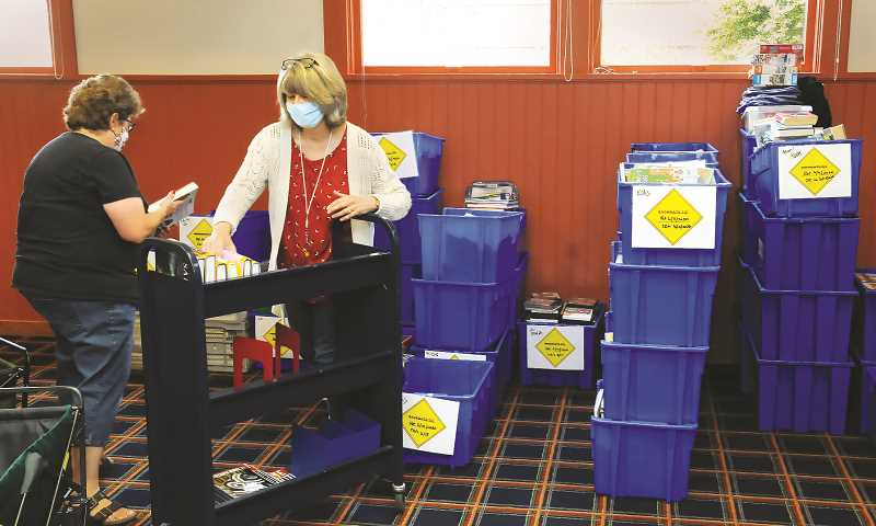 NEWBERG GRAPHIC: GARY ALLEN - Lori Biever-Launder (left) and Cynthia Swanson store away books returned last week. Following state guidelines, the books and other library materials sit for three days before being reshelved in order to ensure they are virus free.