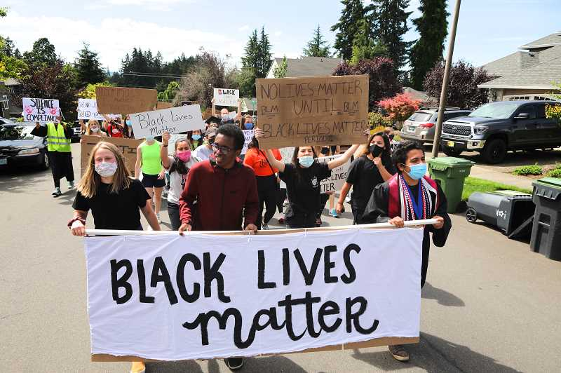 PMG PHOTO: JAIME VALDEZ - Sarah Gentry, left, Abdi Mohamoud and Matt Brown lead a march through a Tualatin neighborhood Thursday afternoon as they head to Tigard High School. The group of marchers, who numbered about 400, were part of a Student March for Black Lives.