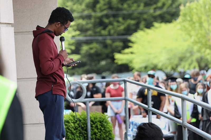 PMG PHOTO: JAIME VALDEZ - Abdi Mohamoud addresses students in the south parking lot of Tualatin High School Thursday afternoon. Part of his address included reading the names of those shot and killed by police.