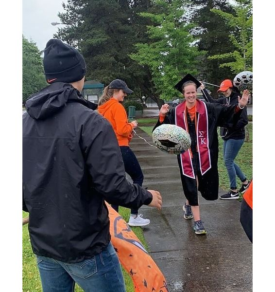 COURTESY PHOTO - Jaclyn Marston high-fives friends and family during her 15-kilometer graduation run.
