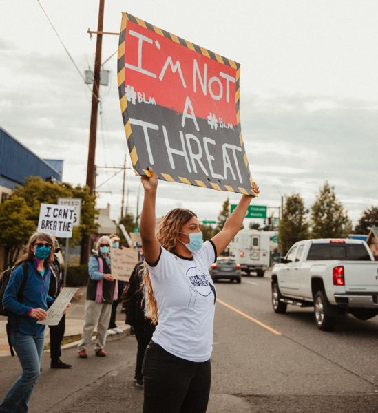 COURTESY PHOTO: REDFRED PRODUCTIONS - Sandy STAND UP Movement co-organizer Tracy George holds a sign at the June 14 march against racism.