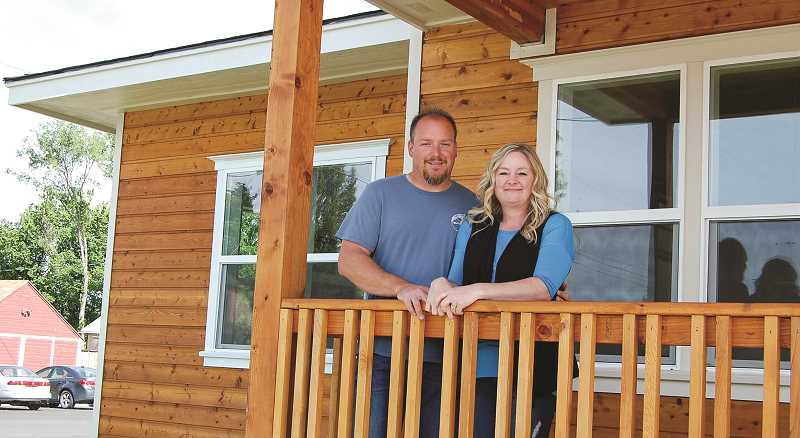 PHOTO COURTESY OF JEREMY GROVER - Jeremy and Mystie Grover stand on the front porch of their recently completed office for Homestead Realty at 195 NW Fifth St.