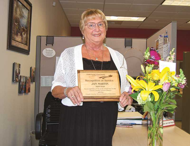 RAMONA MCCALLISTER - Jan Martin proudly holds a plaque and flowers that were presented from the CCSD school board members and district office staff during the last CCSD school board meeting.
