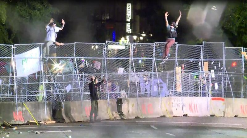 KOIN 6 NEWS - People sit on the fence that lines the Justice Center with their hands up on June 13.