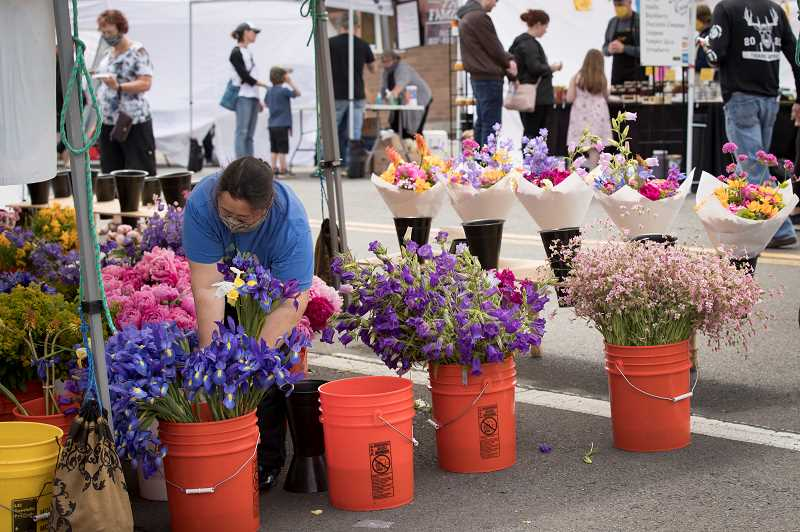 PMG PHOTO: JAIME VALDEZ - A flower seller places a bouquet in water during the Tigard Farmers Market held last weekend on Tigard Street.