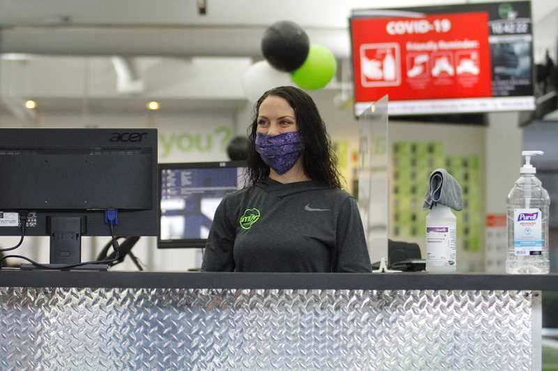 PMG PHOTO: WADE EVANSON - Chanze Patterson helps members at the front desk at Muv Fitness in Tanasbourne.