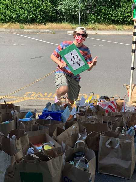 PHOTO COURTESY OF JESSE BRODRICK - Jesse Brodrick, a Wilson High School graduate, used his last days as a senior to organize a food drive to benefit Neighborhood House. Brodrick collected donations during a cap and gown pickup event at the high school.