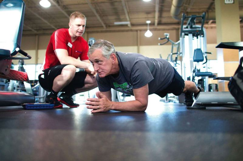 PMG: KEVIN HARDEN  - Bankrupt 24 Hour Fitness is closing its Beaverton adn Vancouver gyms. Here in 2014 then Portland Mayor Charlie Hales does a plank exercise during one of his regular morning sessions at 24 Hour Fitness, as personal trainer Steven Brock checks his form.