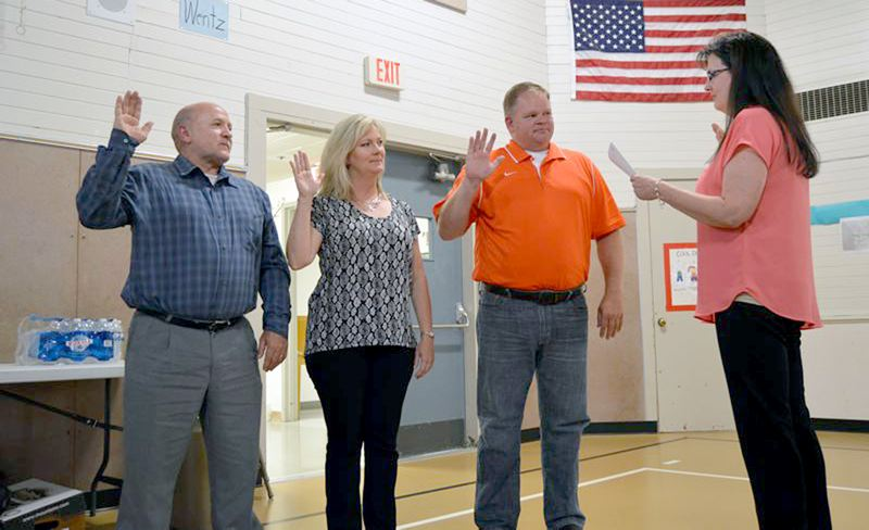 PMG PHOTO: NICOLE THILL - Tim Brooks, left, is sworn in to serve on the Scappoose School Board alongside Lisa Maloney and Phil Lager in June 2017.