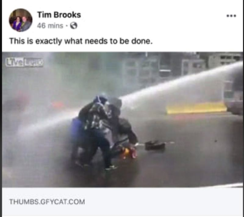 FACEBOOK - A screenshot from Tim Brooks' Facebook account shows him writing 'This is exactly what needs to be done' on a GIF of people being sprayed with high-power water hoses.
