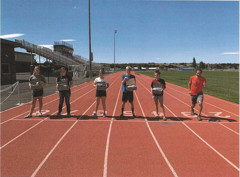 COURTESY PHOTO - Mario Mendoza Jr., far right, stands on the track with Madras High students, each holding Brooks Running shoes. They are, from left, Hanna McDuffee, Hannah Young, Amber Simmons, Jason Symons and Olivia Symons.