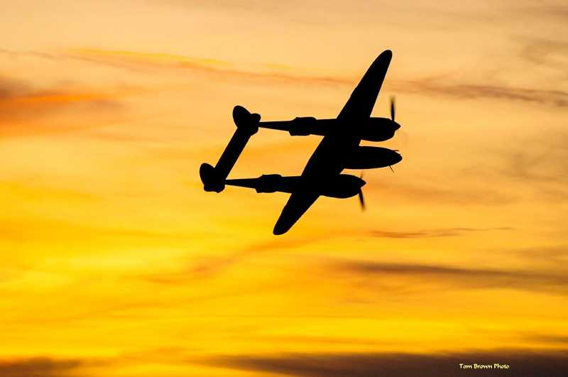 PHOTO BY TOM BROWN - A P-38 Lightning, from the Erickson Aircraft Collection, is silhouetted in the sunset on the opening night of the Airshow of the Cascade in 2019. The show's 20th anniversary is on hold until 2021.