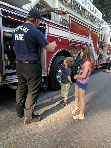 PHOTO COURTESY OF SOUTH BURLINGAME NEIGHBORHOOD ASSOCIATION - A firefighter with Portland Fire and Rescue shows off a fire engine to children during a South Burlingame Neighborhood Association event. Community events and outreach play a key role in neighborhood associations.
