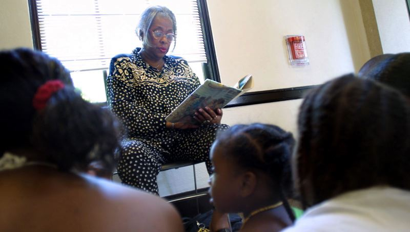 FILE - Leola 'Mother' Veasley reads  'Back Home' by Gloria Jean Pinkney to African-American youths during part of the Juneteenth celebration at the North Portland Branch Library in 2002.