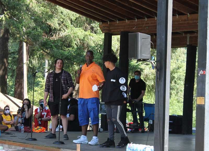 PMG PHOTO: HOLLY BARTHOLOMEW - Michael Fesser (center) who was wrongully arrested by West Linn police in 2017, speaks at a protest in West Linn June 18.
