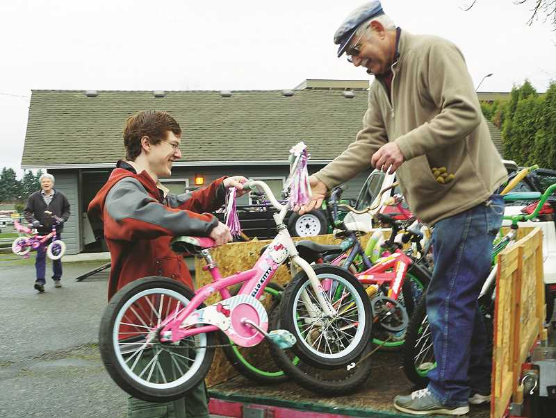 COURTESY PHOTO: CORINNE WATERBURY - Boy Scout Spencer Veatch loads one of the 25 bicycles he collected over the course of five months to a volunteer at the Retired Recyclers headquarters in Newberg.