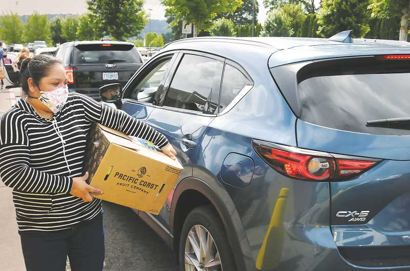 PMG PHOTO: GARY ALLEN - Fifteen volunteers from two Newberg churches delivered 25-pound boxes of fresh food to vehicles on June 16 as part of a USDA program administered across the country.