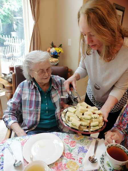 COURTESY PHOTO - Kathy Beck, owner of the Rivercrest senior living facility in Oregon City, serves tea sandwiches to resident Betty Bunch without masks or gloves during the COVID-19 pandemic.