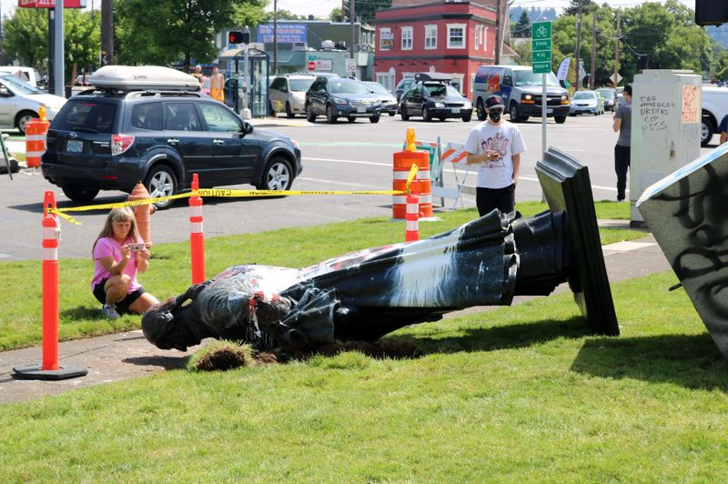 PMG PHOTO: ZANE SPARLING - Onlookers checked out the toppled over statue of George Washington near the German American Society in Northeast Portland on Friday, June 19.