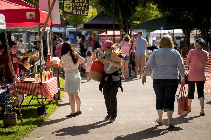 PMG PHOTOS: JAIME VALDEZ - Barbara Holden puts a bottle of honey in her bag as she makes her way through the Wilsonville Farmers Market at Town Center Park.