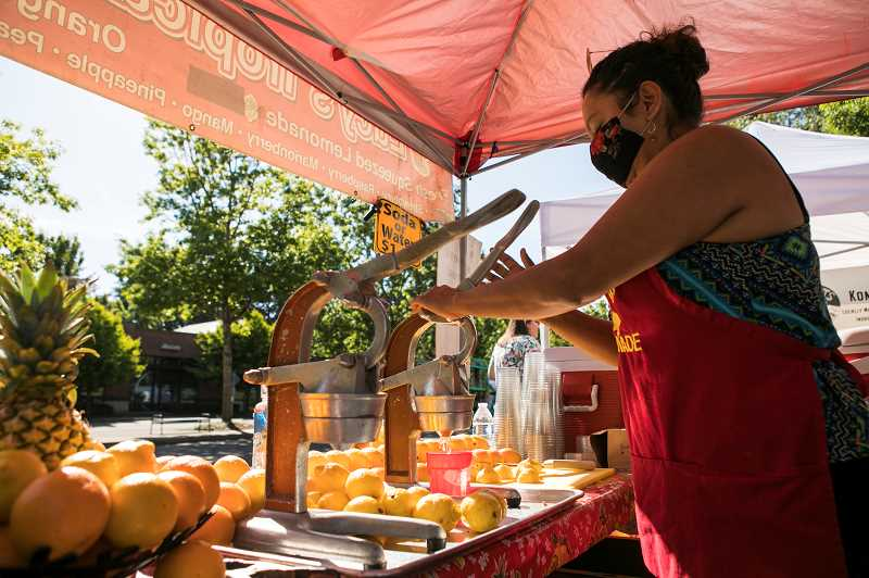 Lucy Contreras, who is the owner of Lucys Tropical Juice, squeezes lemons for the lemonade juices she makes at Wilsonville Farmers Market at Town Center Park.