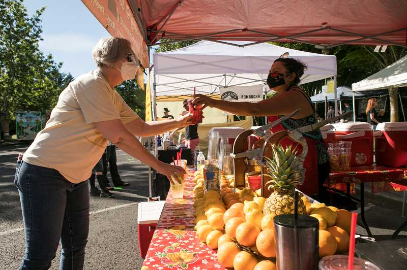 Hilary Melbourne receives a cup of freshly squeezed lemonade from Lucy Contreras' lemonade booth at Wilsonville Farmers Market at Town Center Park.