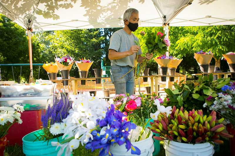 Steve Thao from Sunrise Family Farm makes a flower bouquet for customers at the Wilsonville Farmers Market at Town Center Park.