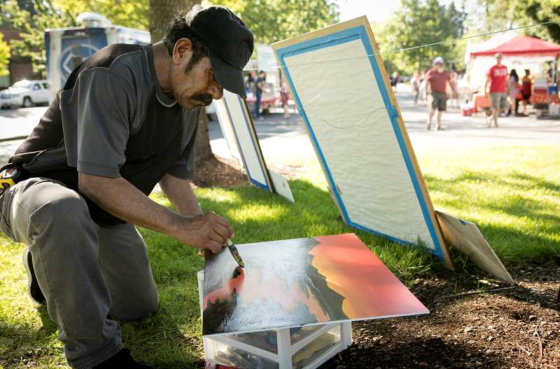 Juan Mendoza Pintor paints a scenic to sell at the Wilsonville Farmers Market at Town Center Park.