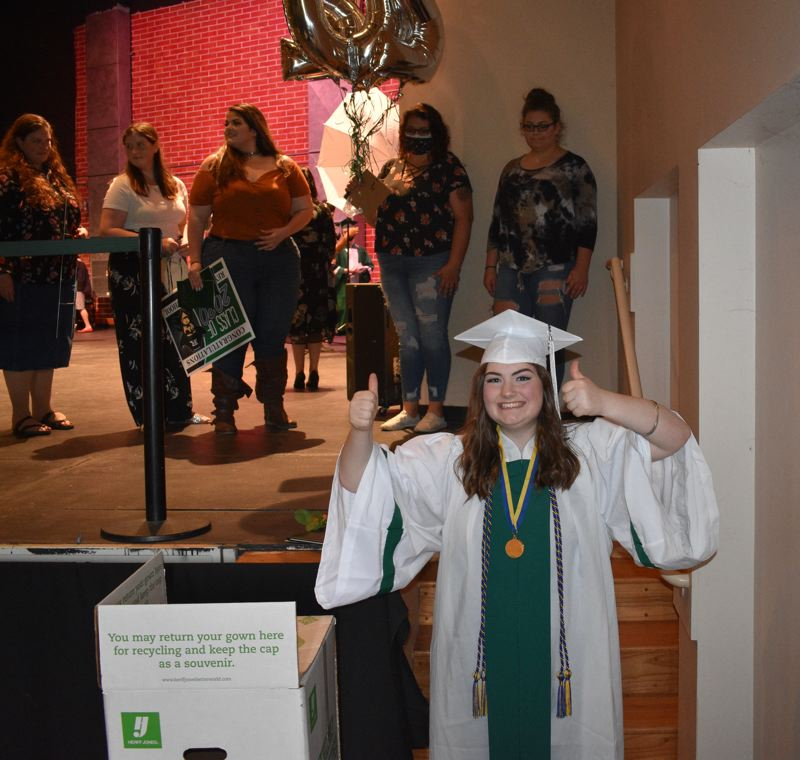 PMG PHOTO: TERESA CARSON - Jaclyn Hamilton, with her family in the background, gives a thumbs up at Reynolds High School graduation ceremonies