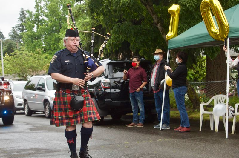 PMG PHOTO: CHRISTOPHER KEIZUR - A bagpiper stopped to play the birthday song during a parade in honor of Francisco Villavicencios milestone birthday.