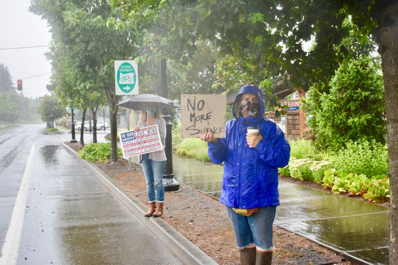 PMG PHOTO: EMILY LINDSTRAND - Demonstrators hold signs during Estacada's demonstration in support of the Black Lives Matter movement on Saturday, June 20.