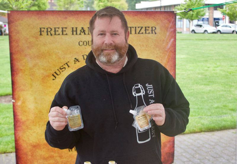 PMG PHOTO: CHRISTOPHER KEIZUR  - John HasBrouck has been handing out hand sanitizer he makes at the Just Rum distillery at the Gresham Farmers Market since its opening day.