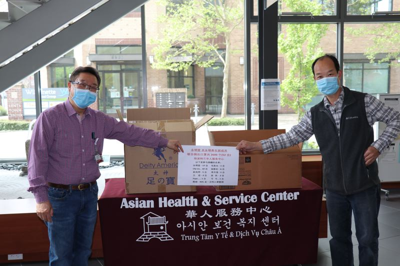 COURTESY PHOTO: ASIAN HEALTH AND SERVICE CENTER - Holden Leung, executive director of the Asian Health and Service Center, receiving a donation of 2,600 medical masks from Ken Yue, owner of Portland-based business Wing Ming Herbs.