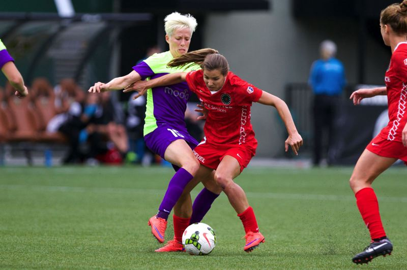 PMG FILE PHOTO: JAIME VALDEZ - The Thorns Tobin Heath and Reign's Megan Rapinoe battled in this 2015 match, but neither will participate in the NWSL Challenge Cup.